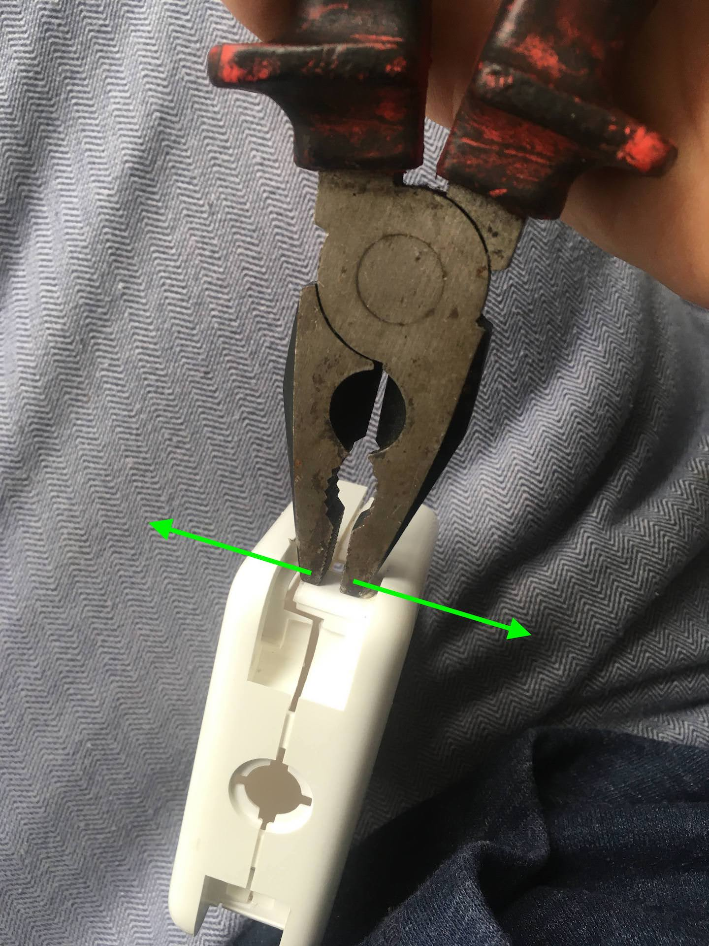 Using flat head pliers to open a MacBook Charger